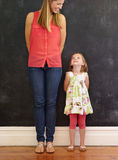 Little girl standing with her mother at home Stock Images