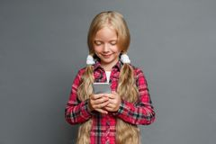 Little girl standing isolated on grey browsing smartphone happy royalty free stock photos