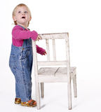 Little girl standing keeping old white chair Royalty Free Stock Photography