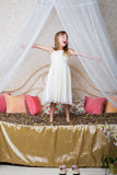 A little girl standing on the large bed Royalty Free Stock Images