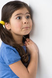 Little girl standing and leaning against wall. Royalty Free Stock Photo