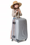 Little girl standing leaning on a suitcase Stock Images
