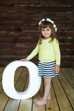 Little girl standing near the big letter O. Portrait of a little girl standing near the big letter O. A wooden background Stock Images