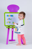 A little girl is standing near the board with letters and numbers. The school is written on the blackboard Stock Photography