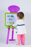 A little girl is standing near the board with letters and numbers. The school is written on the blackboard Royalty Free Stock Photography
