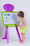 A little girl is standing near the board with letters and numbers. The school is written on the blackboard Royalty Free Stock Images