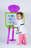 A little girl is standing near the board with letters and numbers. The school is written on the blackboard Royalty Free Stock Photo