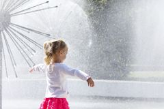 Little girl standing near the dandelion fountain. Royalty Free Stock Images