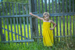 Little girl standing near fence in the village. Walking. Stock Image