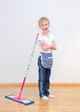 Little girl standing near mop at home. Stock Photography