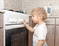 Little girl standing near  stove. Stock Images