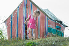 Little girl standing near striped vintage camping canvas tent Stock Photography