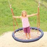 Little girl standing on a net swing Stock Photography