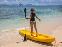 Little girl standing next to colorful yellow kayak Stock Photography