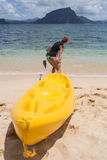 Little girl standing next to colorful yellow kayak Stock Image