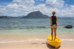 Little girl standing next to colorful yellow kayak Royalty Free Stock Photo