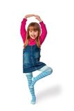 Little girl standing on one leg, isolated Stock Images
