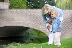 Little girl standing outdoors with grandmother in park Stock Photo