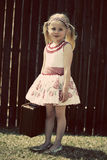 Little girl standing outside smiling at camera. Little girl with blonde hair,pigtails,wearing summer dress standing outside smiling at camera holding a suitcase Stock Images