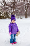 Little girl standing outside in snow. Winter cold weather. Stock Images
