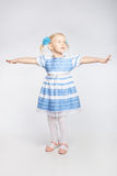 Little girl standing with outstretched arms. Little blonde girl standing with outstretched arms on a white background Stock Photography