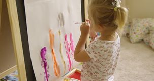 Little girl standing painting at an easel stock video