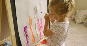 Little girl standing painting at an easel Royalty Free Stock Photography