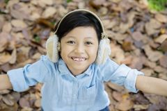 Little girl standing in the park at autumn season. Top view of little girl wearing earmuff while standing in the park with autumn foliage Royalty Free Stock Image