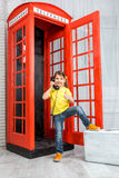 Little girl standing at a phone booth Royalty Free Stock Image