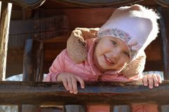 A beautiful caucasian happy blond girl child laughing and looking out of the window of her wooden house in the garden outdoors stock image