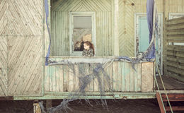 Little girl standing on porch of abandoned cabin Royalty Free Stock Image