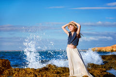 Little girl standing and posing on the beach on the background of the spray and looks at the sun. His hands behind his head, wearing a white skirt and a pillbox Stock Photography