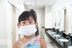 Little girl standing in protective mask,. White mask, bad smell public toilet Stock Photos
