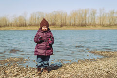 Little girl standing on a riverbank Stock Images