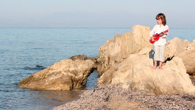 Little girl standing on a rock and playing guitar Stock Photo
