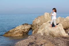 Little girl standing on a rock and playing saxophone Stock Images