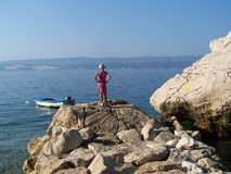 Little girl standing on the rocks watching the sea. Wild rocky beach in Croatia, with a small girl standing and watching the calm sea Royalty Free Stock Photography