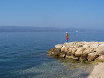 Little girl standing on the rocks watching the sea. Wild rocky beach in Croatia, with a small girl standing and watching the calm sea Stock Photo