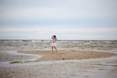 Little girl standing at sandy seashore Stock Photography