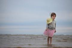 Little girl standing at sandy seashore Royalty Free Stock Photo