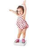 A little girl is standing on the scales Royalty Free Stock Photo