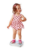 A little girl is standing on the scales Royalty Free Stock Photography
