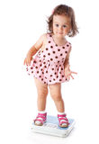 A little girl is standing on the scales Royalty Free Stock Photos