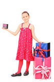 Little girl standing by a stack of presents Royalty Free Stock Photography