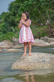 Little girl standing on stone. In a forest stream stock images