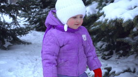 Little girl standing on the street in the winter near Christmas trees stock video