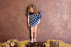 Little girl standing on suitcase in retro style Royalty Free Stock Photos