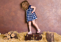 Little girl standing on suitcase in retro style Stock Photo