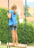Little girl standing on a swing Royalty Free Stock Photo