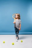Little girl standing with tennis raquet and balls on blue Royalty Free Stock Image